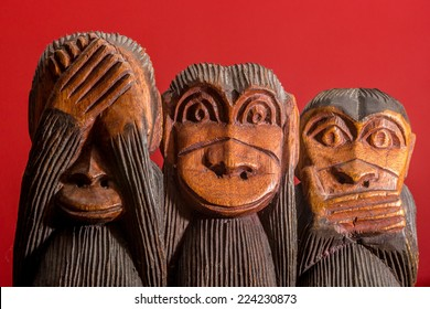 See hear speak no evil carved wooden monkeys on red background facing front