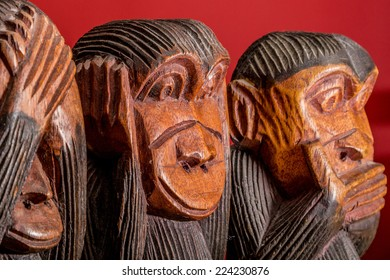 See hear speak no evil carved wooden monkeys on red background close up