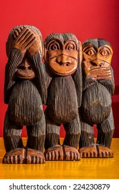 See hear speak no evil carved wooden monkeys on red background full body facing front