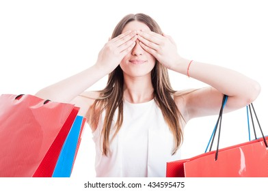 See no evil concept with smiling shopaholic woman covering her eyes and holding colored bags isolated on white studio background