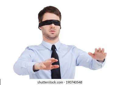 See no opportunity. Young businessman in blindfold stretching out hands while standing isolated on white