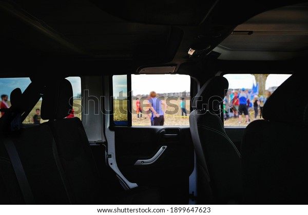 See through view of car interior and side window with group of people attending outdoor event outside. Very unique composition and point of view. Travel, outdoor activities, transportation vehicle.