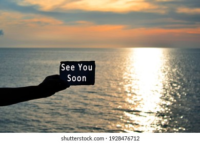 See you soon text on hand holding torn paper with blurred background of sunset at the beach of Tanjung Aru Beach, Kota Kinabalu, Borneo,Sabah, Malaysia