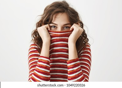 I see you. Studio shot of emotive joyful woman in trendy striped sweater hiding face in it and glancing through collar, smiling and being in playful mood, standing over gray background.