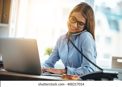 See you tomorrow! Cheerful young beautiful woman in glasses talking on the phone and using laptop with smile while sitting at her working place