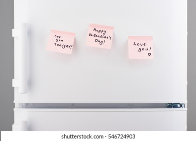 See you tonight, happy valentines day, love you notes on light pink sticky paper on white refrigerator door