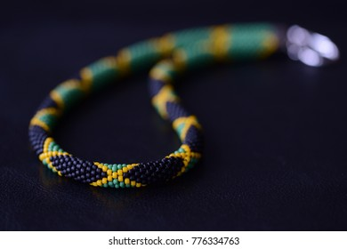Seed beads necklace Jamaican flag on a dark background close up