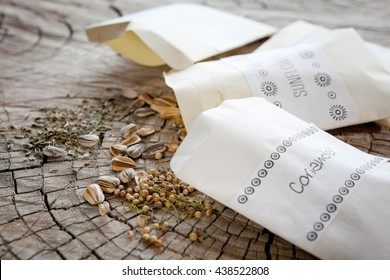 Seed packets and seeds. Focus on coriander and sunflower seeds, dill seeds farther back.
