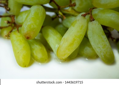 Seedless Green Grape also known as Witch Finger or Cotton Candy, closeup against on white background.