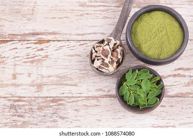 Seeds, leaves and moringa powder. Wooden background - Moringa oleifera