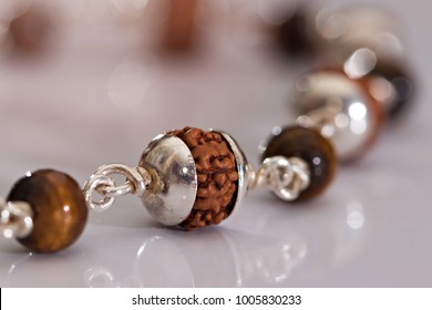 Seeds of the sacred Rudraksha, silver bracelet, beads used by Hindus and Buddhists on white. Macro close up and blur light bokeh background.
