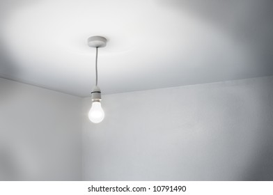 A seedy corner of a room lit by a single bare lamp