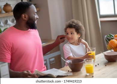 Such die Wange. Dunkelhaariger, afrikanischer Vater berührt seine Töchter Wange und lächelnd