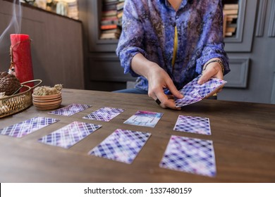 Seeing the destiny. Close up of tarot cards being in female hands while having a fortune telling session