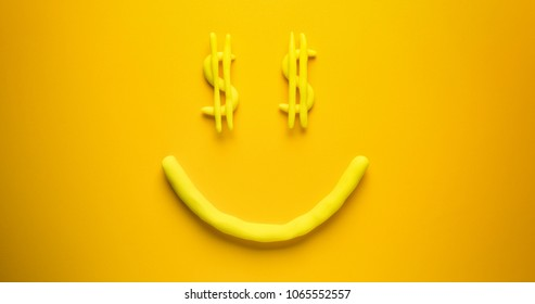 Seeing dollar signs face - a yellow emoticon make out of modelling clay on a yellow background.