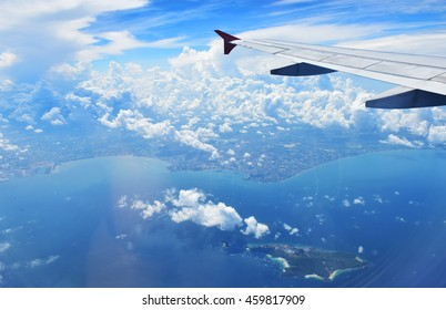 Seeing land from blue sky with airplane wing