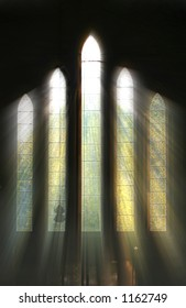 Seeing the light, shafts of sunshine stream through stained glass window and onto cross below