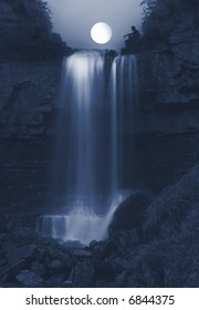 Seeing the light, young Man  sitting  on rocks on the top of the powerful Ashgill Waterfall in England lit by the Moon