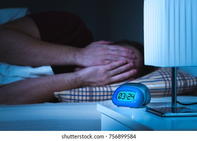 Seeing nightmares or bad dreams concept. Scared man covering face with hands in bed. Alarm clock on nightstand in bedroom.