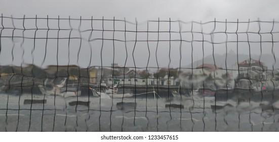 Seeing the rain falling through the car windshield.