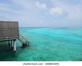 seeing wood stairs down from balcony to ocean floor. Underwater reefs can also be seen under clear blue sea water and the sky is clear with cloud