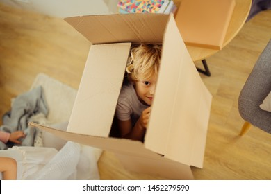 Seek and hide. Positive nice boy hiding in a box while playing seek and hide