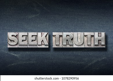 seek truth phrase made from metallic letterpress on dark jeans background