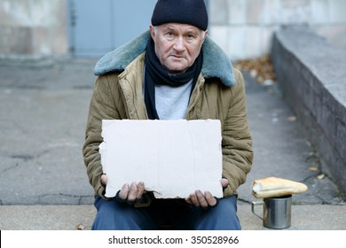 Seeking help. Sad exhausted old-aged man is sitting outside and holding a cardboard sign.