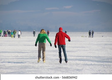 Seekirchen, Austria - January 29, 2017: On the frozen lake Wallersee in Seekirchen. A couple is skating on the ice. Salzburger Land, Austria, Europe.