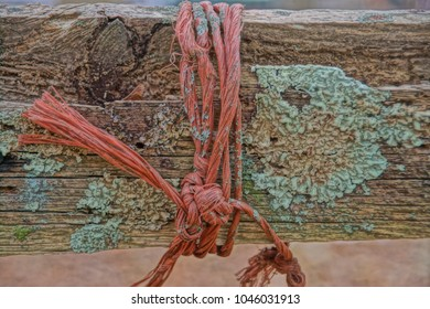 Seekonk, Massachusetts/USA- January 3, 2018: An orange piece of twine is wrapped and knotted around a decaying wooden rail.