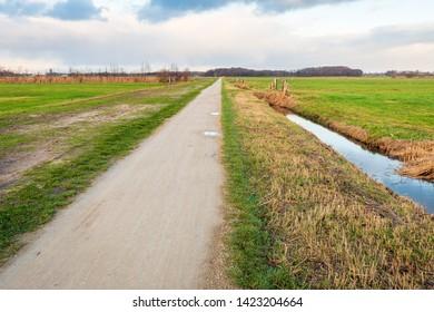 Seemingly endless straight path in a rural polder landscape on a cloudy day in the Dutch winter season. The phot was taken in the Binnenpolder near the village of Terheijden, Drimmelen, North Brabant.