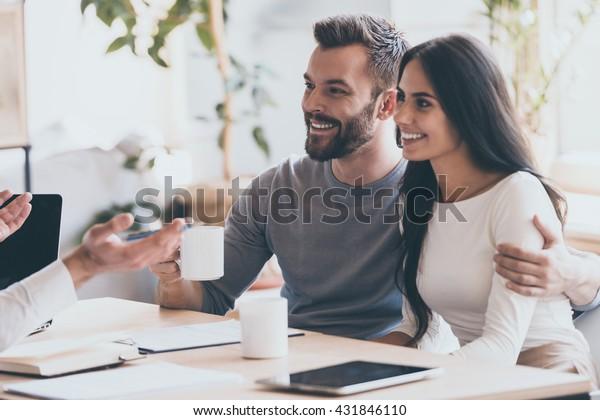 Es scheint ein guter Vorschlag zu sein. Fröhliches junges Paar, das sich gegenseitig anbindet und lächelt, während es einen Mann ansieht, der vor ihm sitzt und gesinnt