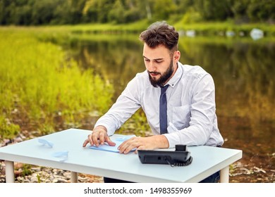 It seems to the white collar that he is not in the office, but somewhere near the river, in the forest. An office worker sits at a table with a paper and phone and fantasizes that he is in the wild.