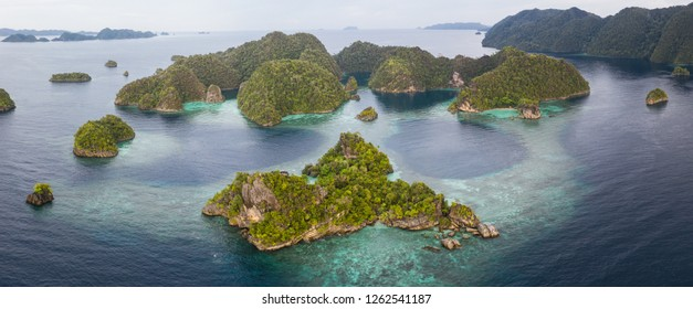 "Seen from above, a shallow coral reef surrounds remote islands in Raja Ampat, Indonesia. This biodiverse region is known as the ""heart of the Coral Triangle"" due to its amazing marine life."