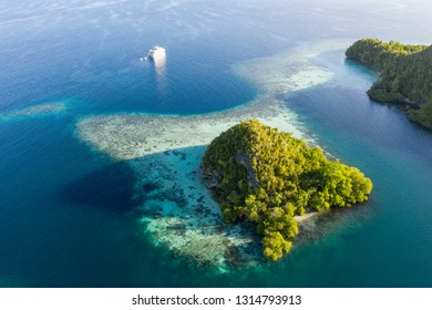 Seen from the air, early morning light illuminates limestone islands found in Raja Ampat, Indonesia. This remote, tropical region is known for its incredible marine biodiversity.