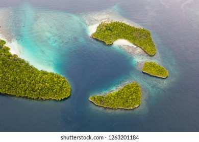 "Seen from the air, tropical islands are surrounded by coral reefs in Raja Ampat, Indonesia. This biodiverse region is known as the ""heart of the Coral Triangle"" due to its amazing marine life."