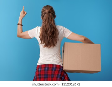Seen from behind active woman in white shirt with a cardboard box pointing up at copy space isolated on blue