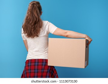 Seen from behind active woman in white shirt with a cardboard box against blue background