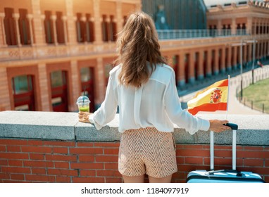 Seen from behind elegant traveller woman with trolley bag, Spain flag and green smoothie near Puerta De Atocha train station building