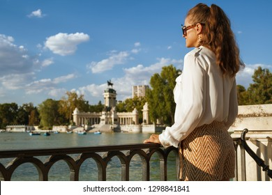 Seen from behind elegant traveller woman in white blouse and shorts at Buen Retiro Park in Madrid, Spain looking into the distance. сaucasian woman brunette ponytail hairstyle 30 something years old.