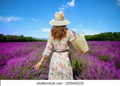 Seen from behind elegant woman in floral dress with straw bag at lavender field in Provence, France. Save time for leisurely promenade among colorful and vibrant lavender on fields of Apt and Gordes