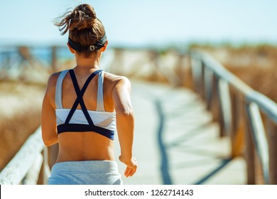 Seen from behind fit sports woman in fitness clothes on the ocean shore running. hone your form and speed at ocean shore resistance workout.