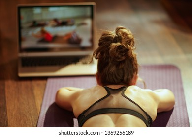 Seen from behind fit sports woman in fitness clothes in the modern living room using online fitness training program in laptop while laying on fitness mat.