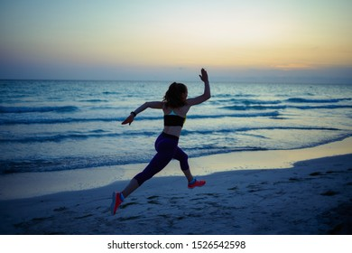 Seen from behind fit sports woman in sport style clothes on the ocean shore in the evening jogging.