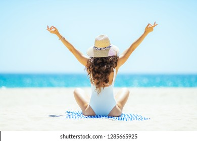 Seen from behind healthy woman in white swimwear on the ocean coast rejoicing while sitting on a striped towel. woman wearing straw hat. spending hours at the beach. Sunny summer midday.