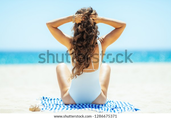 Seen from behind healthy woman in white swimwear on the ocean shore siting on a striped towel. Sun protected hair. spending hours at the beach.