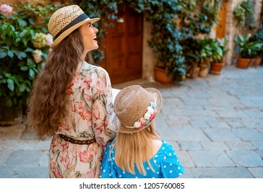 Seen from behind modern mother and daughter travellers in old Europe town exploring attractions