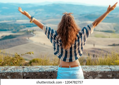 Seen from behind modern traveller woman in striped blouse rejoicing against scenery of Tuscany