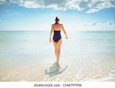 Seen from behind modern woman in swimsuit on the seashore going into the sea
