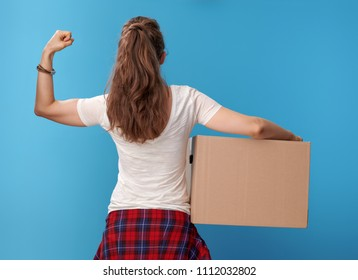 Seen from behind modern woman in white shirt with a cardboard box showing biceps isolated on blue background